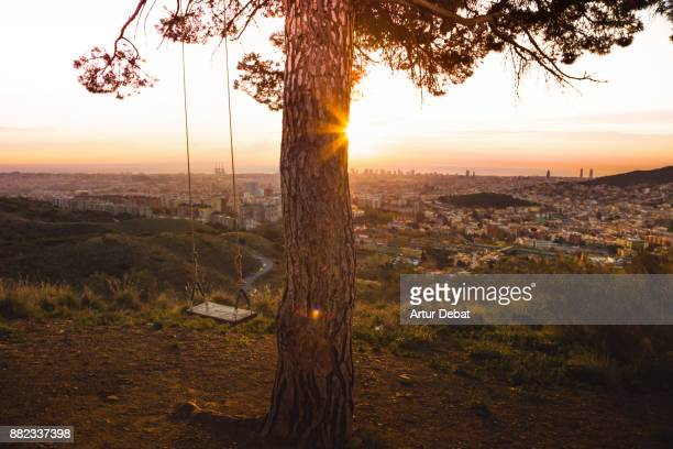 The sunrise over Barcelona city from cool viewpoint with unique perspective of the city, with empty swing and the view from lonely tree in the Collserola mountains.