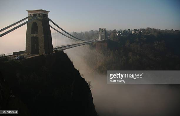 The sun's rays begin to clear the early morning mist around Clifton Suspension Bridge on February 13 in Bristol United Kingdom Spanning the Avon...