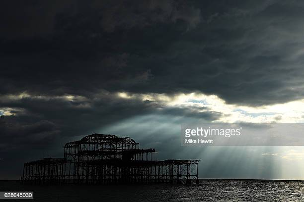 The Sun's rays light up the derelict West Pier which sits off the coast adjacent to the brand new British Airways i360 Tower on December 1 2016 in...