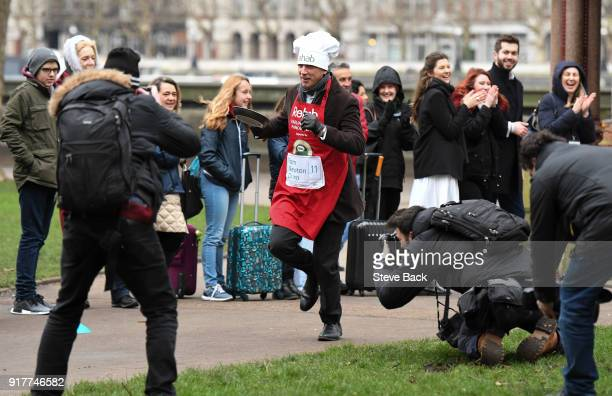 The Sun's Tom Newton Dunn approacheses the first corner in the annual Parliamentary Pancake Race in Victoria Tower Gardens on Shrove Tuesday on...
