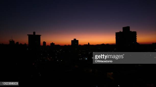 the sunset and the silhouette of the city. - crmacedonio stock-fotos und bilder