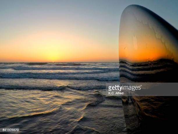 The sunset is reflected in a paddle in the La Jolla Shores Beach area of San Diego, California.