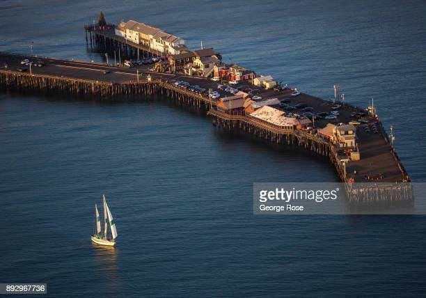 The Sunset Kidd a charter tour sailboat heads out past Stearn's Wharf and into open water in this sunset aerial photo taken on December 4 over Santa...