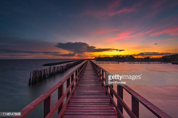 the sunset on the wooden bridge into the sea near bangkok, thailand - prachuap khiri khan province stock pictures, royalty-free photos & images
