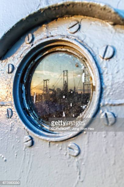 The sunset reflected on the round window of a ship