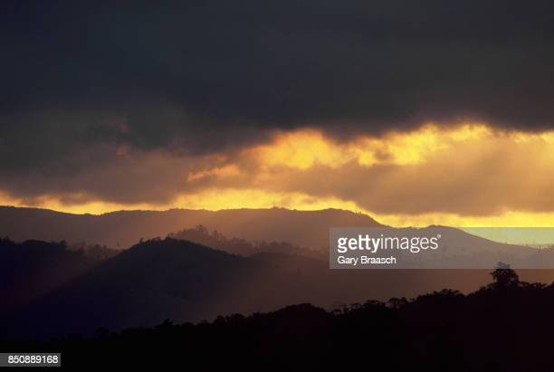 The sunset silhouttes the mountains around Lake Arenal under a thick cloud cover Costa Rica | Location Lake Arenal Costa Rica