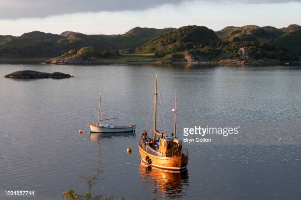 The sunsets on Duntrune Castle and boats moored on Loch Crinan on August 19, 2021 in Crinan, Scotland. Passage along the canal has been reduced as...