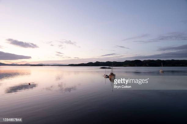 The sunsets over boats on Loch Crinan on August 19, 2021 in Crinan, Scotland. Passage along the canal has been reduced as water levels run low due to...