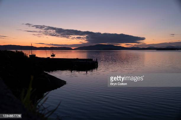 The sunsets over the harbour at Loch Crinan and the Isle of Jura on August 19, 2021 in Crinan, Scotland. Passage along the canal has been reduced as...
