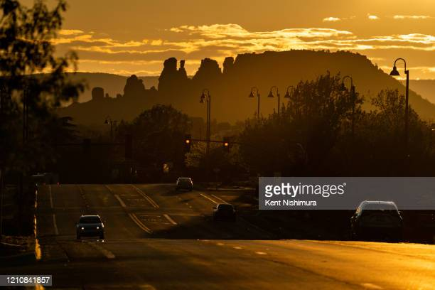The sunsets over the normally streaming with traffic Arizona State Route 89A cutting through Sedona sees a traffic trickle down the route with...