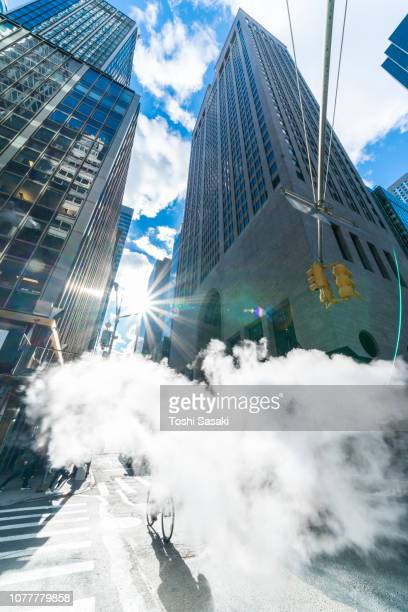 The sunshine above the skyscrapers illuminates the drifting steam among the Midtown Manhattan high-rise buildings at New York NY USA on Nov. 23 2018.