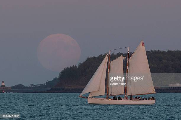 The Super Blood Moon rises over a sailboat in Boston Harbor on September 27 2015 in Boston Massachusetts The Super Moon coincides with a total lunar...