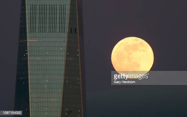 The Super Blood Wolf Moon rises behind One World Trade Center in New York City on January 20 2019 as seen from Jersey City New Jersey