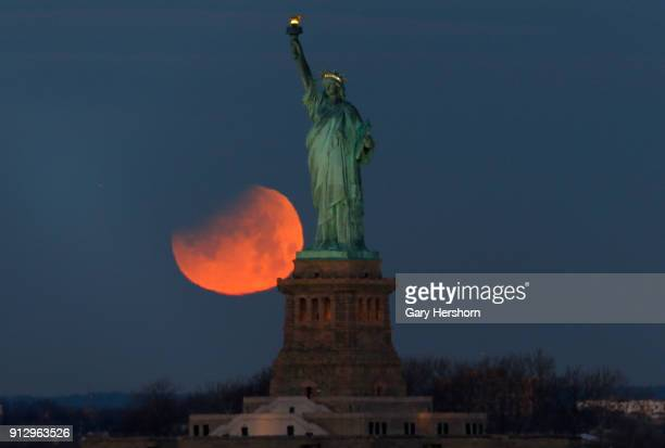 The super blue blood moon is partially eclipsed as it sets beside the Statue of Liberty on January 31 2018 in New York City