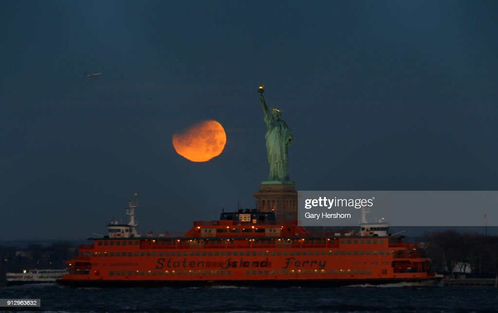 The super blue blood moon is partially eclipsed as it sets beside the Statue of Liberty on January 31, 2018 in New York City.