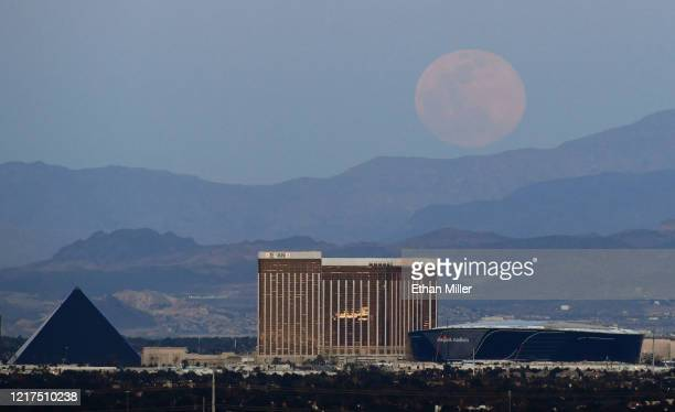 The super pink moon, the biggest supermoon of the year, rises over Luxor Hotel and Casino, Delano Las Vegas at Mandalay Bay Resort and Casino,...