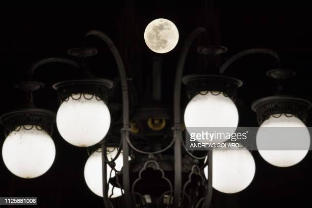 The Super Snow Moon is pictured against street lights of Piazza del Duomo in downtown Milan on February 19 2019