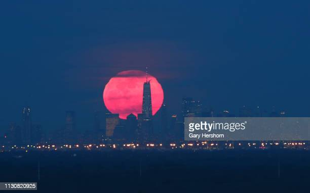 The super snow moon rises behind lower Manhattan and One World Trade Center in New York City on February 19 2018 as seen from Green Brook Township...