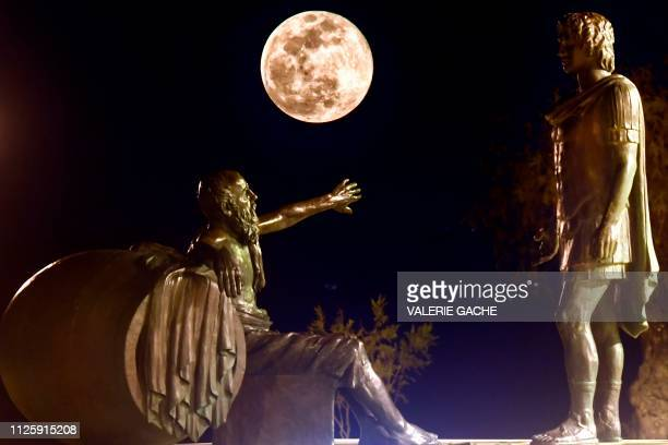 TOPSHOT The Super Snow Moon rises between the statues of Alexander the Great and Diogenes of Sinope in Corinth 83 km from Athens on February 19 2019