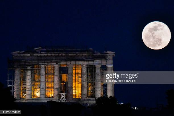 The Super Snow Moon rises next to the Parthenon Temple at the Acropolis archaeological site on February 19 2019 Super Moon is a term used with a full...