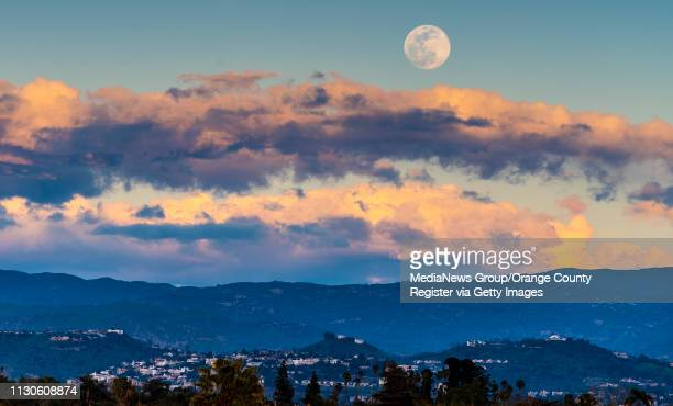 The super snow moon seen from Santa Ana College as it rises above the clouds at sunset in Santa Ana on Monday February 18 2019