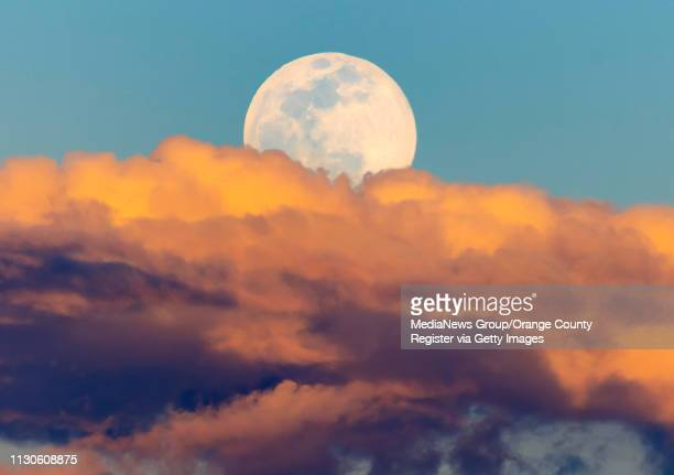 The super snow moon seen from Santa Ana College rises above the clouds at sunset in Santa Ana on Monday February 18 2019