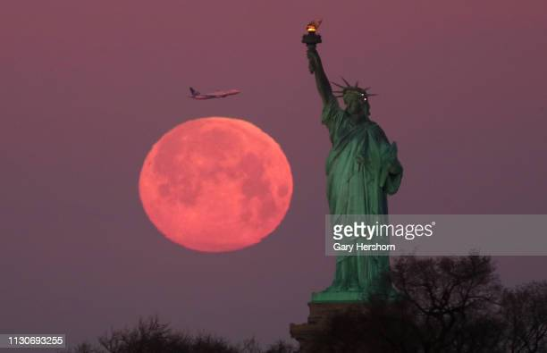 The Super Snow Moon sets behind the Statue of Liberty as the sun rises on February 19 in New York City
