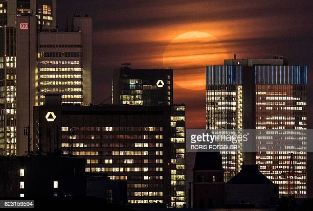 The 'supermoon' is covered by clouds behind the skyline of Frankfurt am Main Germany on November 14 2016 The unusually big and bright moon appeared...