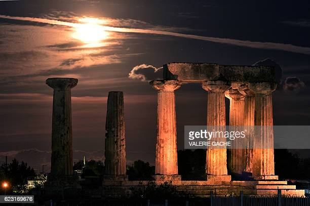 The 'Supermoon' is pictured above the Temle of Apollo in Ancient Corinth on November 14 2016 Skygazers headed to highrise buildings ancient forts and...
