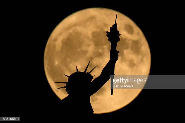 The supermoon is seen above a statue at the top of the Nature and History Museum on November 14 2016 in Vienna Austria The unusually big and bright...