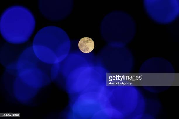 The supermoon is seen behind blurred spotlight reflections in Hatay Turkey on January 03 2018 A supermoon is a full moon that almost coincides with...