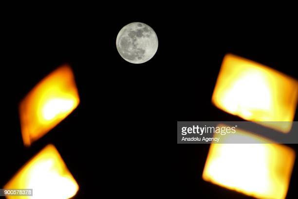 The supermoon is seen behind spotlights in Hatay Turkey on January 03 2018 A supermoon is a full moon that almost coincides with the closest distance...