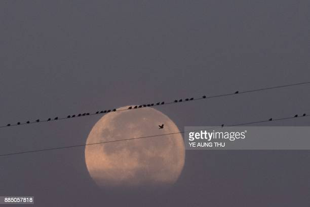 The supermoon is seen next to electric lines near Yangon on December 4 2017 / AFP PHOTO / YE AUNG THU