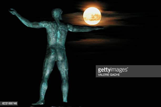 TOPSHOT The 'Supermoon' rises above the statue of the ancient Greek god Poseidon in Ancient Corinth on November 14 2016 Skygazers headed to highrise...