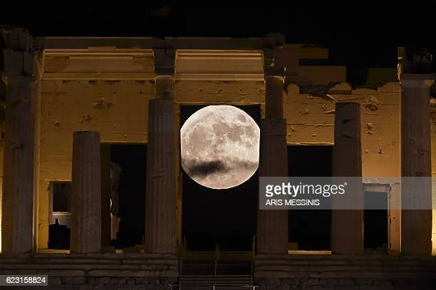The 'Supermoon' rises behind the Propylaea above the Ancient Acropolis hill in Athens on November 14 2016 The moon will be the closest to Earth since...