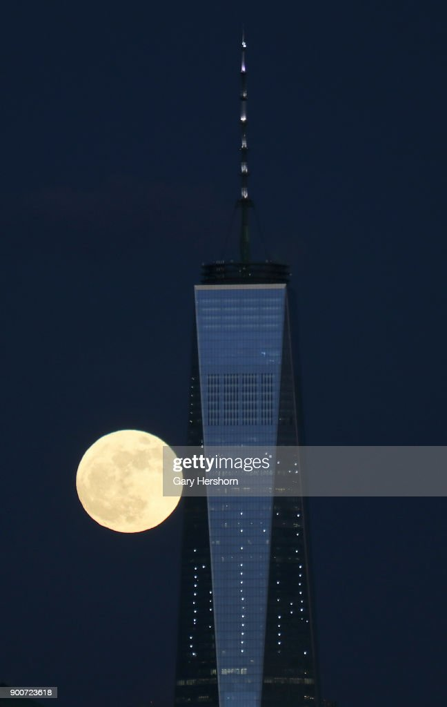 The supermoon rises behind the skyline of lower Manhattan and One World Trade Center in New York City on January 1, 2018 as seen from Jersey City, New Jersey.