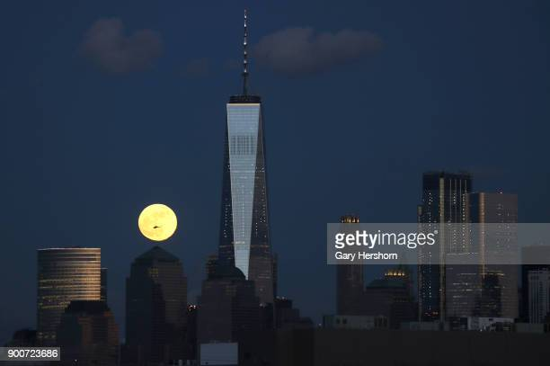 The supermoon rises behind the skyline of lower Manhattan and One World Trade Center in New York City on January 1 2018 as seen from Jersey City New...