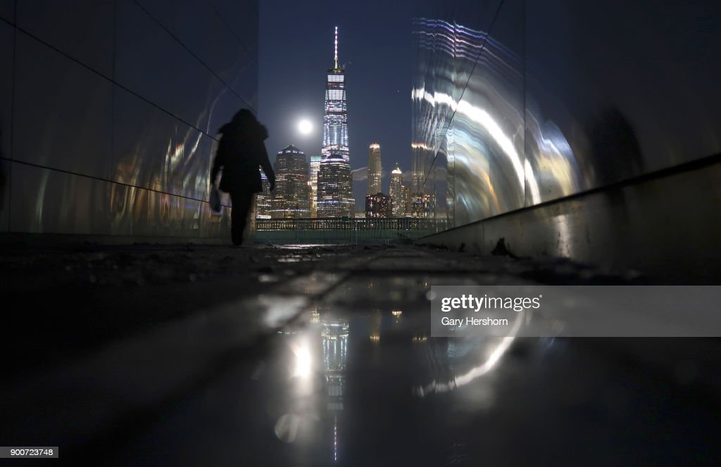 The supermoon rises behind the skyline of lower Manhattan and One World Trade Center in New York City on January 1, 2018 as seen from the Empty Sky 9/11 Memorial in Jersey City, New Jersey.