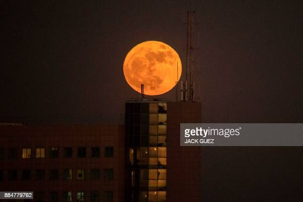 The 'supermoon' rises over a building in the Israeli city of Netanya on December 3 2017 The lunar phenomenon occurs when a full moon is at its...