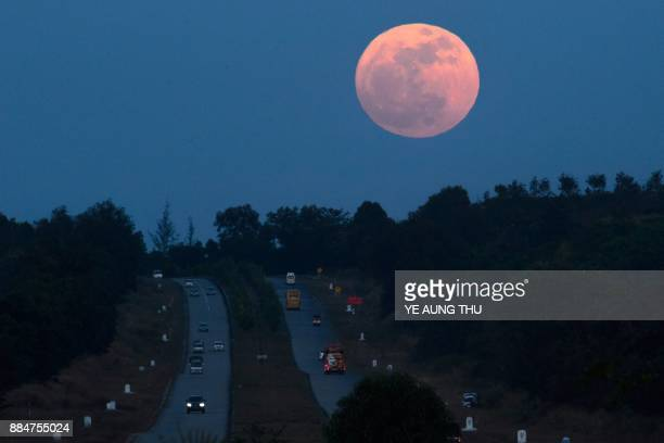 TOPSHOT The supermoon rises over a highway near Yangon on December 3 2017 The lunar phenomenon occurs when a full moon is at its closest point to...