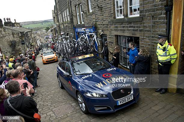 The support car for Team Wiggins follows the peloton up a cobblestone street through the village of Haworth during the third and final day of the...