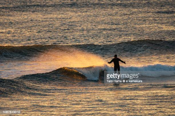 The surfer riding on the sunset wave in Kamakura in Japan