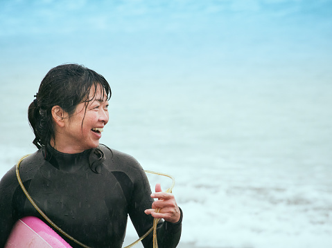 The surfer's woman is smiling at the sea - gettyimageskorea