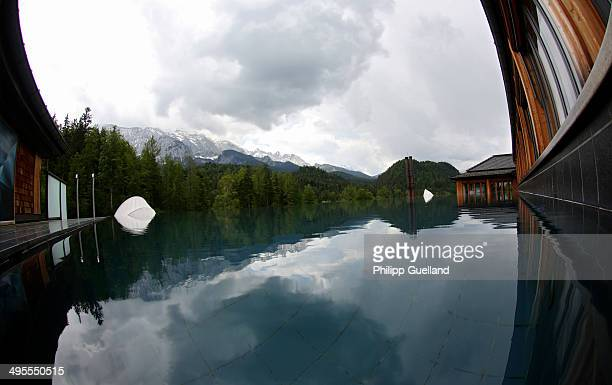 The surrounding landscape is reflected in a rooftop pool at Schloss Elmau, a luxury spa hotel, in the Bavarian Alps of southern Germany on June 3,...