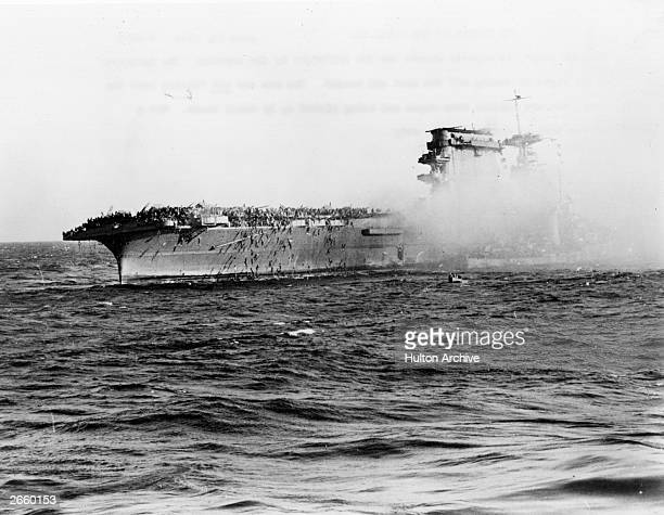 The surviving crew of USS Lexington sunk by the Japanese in the Coral Sea abandon ship Sailors slide down ropes and are picked up by small boats the...
