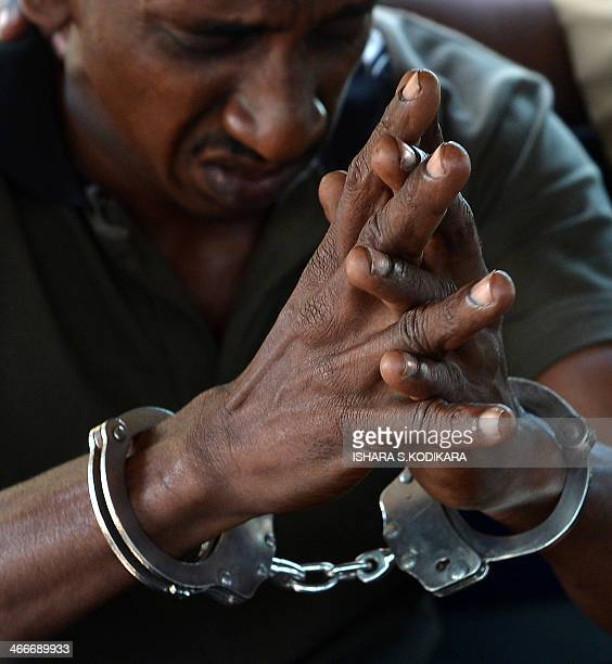 The suspect arrested in connection with the murder of former Agence FrancePresse journalist Mel Gunasekera sits with handcuffs at a police station in...