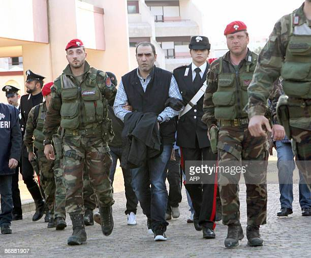 The suspected head of a Calabrian mafia crime family 'Ndrangheta Salvatore Coluccio is escorted by police special forces following his arrest on May...