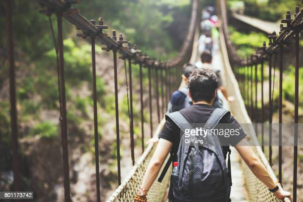 the suspension bridge in the forest - suspension bridge stock photos and pictures