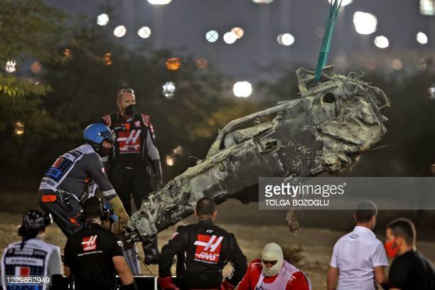 The suvival cell of Haas F1's French driver Romain Grosjean's car is removed after a crash during the start of the Bahrain Formula One Grand Prix at...