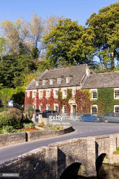 The Swan Hotel beside the River Coln in the Cotswold village of Bibury, Gloucestershire UK